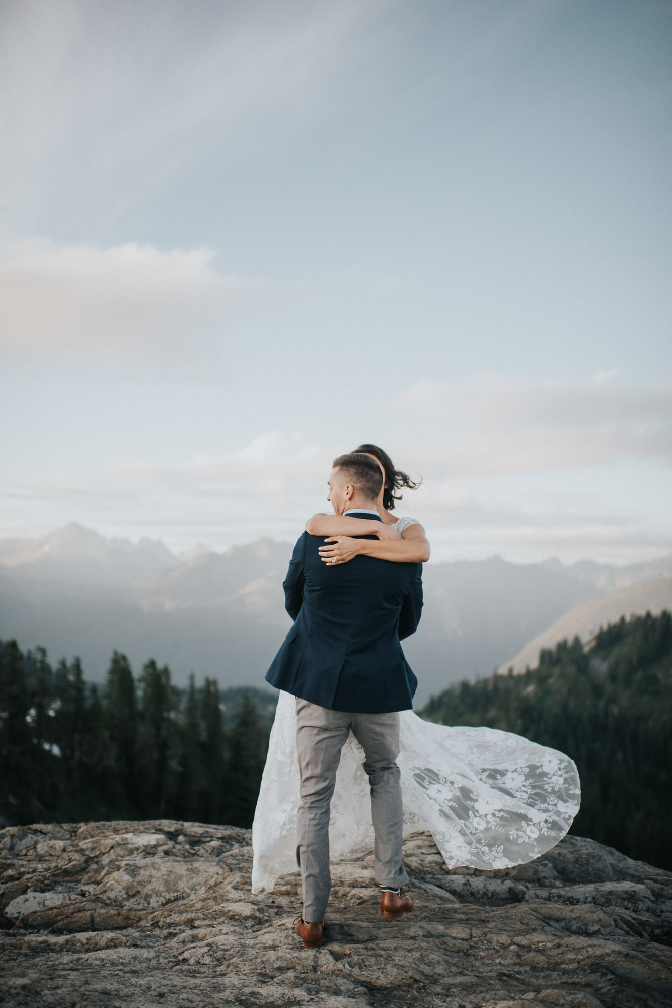 groom spinning bride on top of a mountain