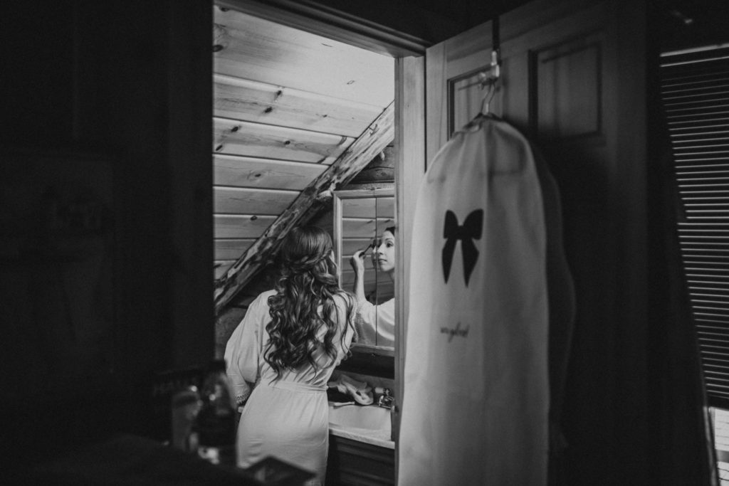 Bride putting eye makeup on in the mirror