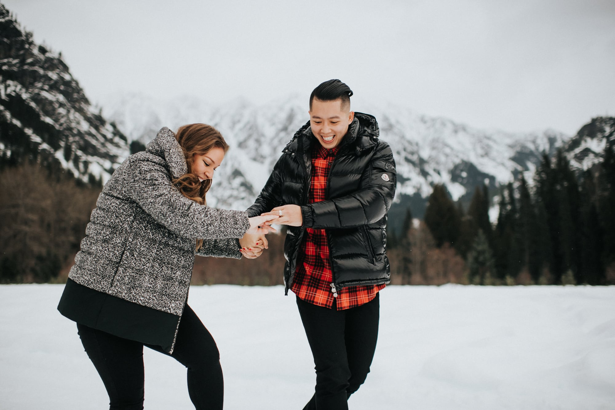 couple playing in the snow during their engagement photos