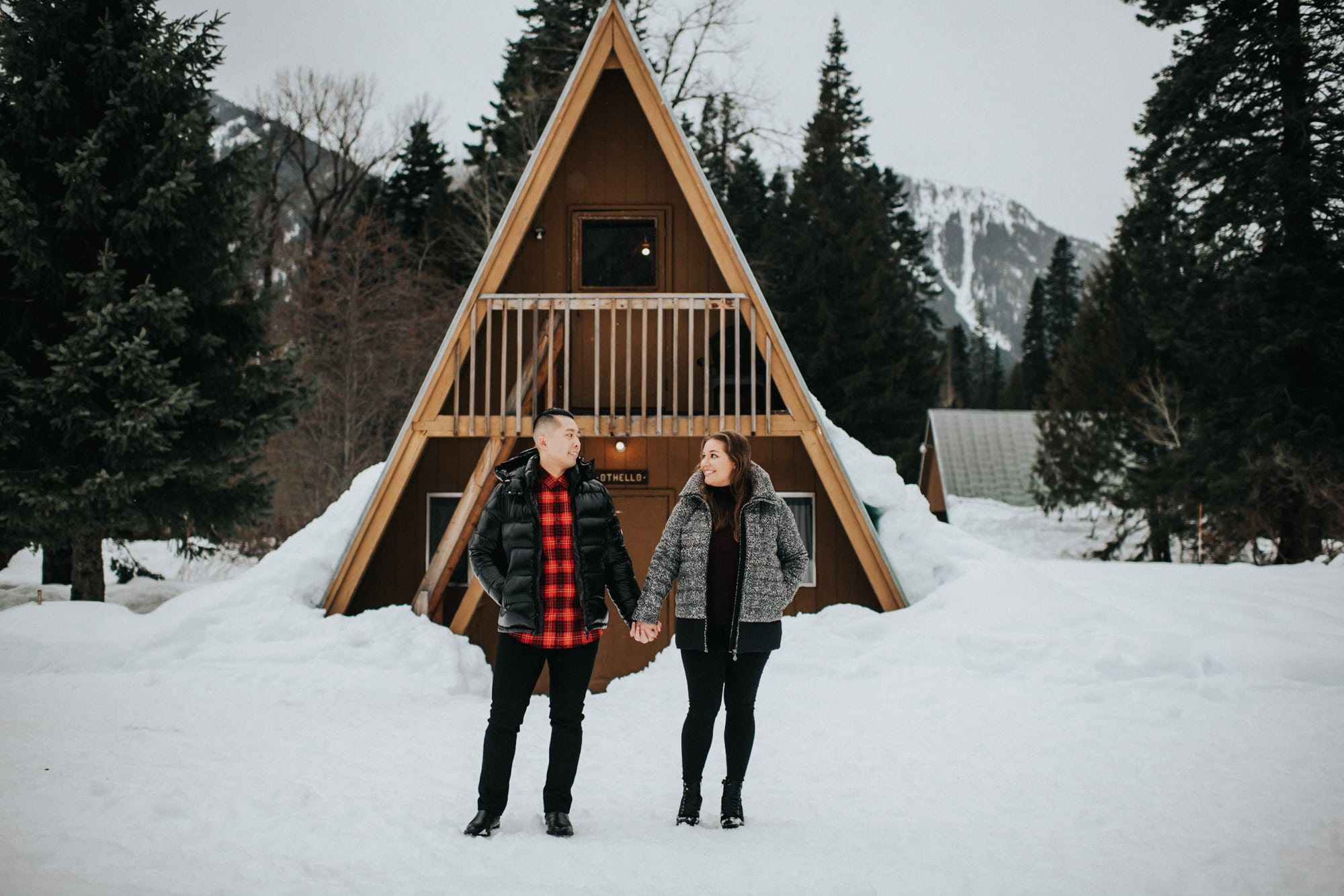 couple engagement photos in from of a-frame cabin at tall timber ranch