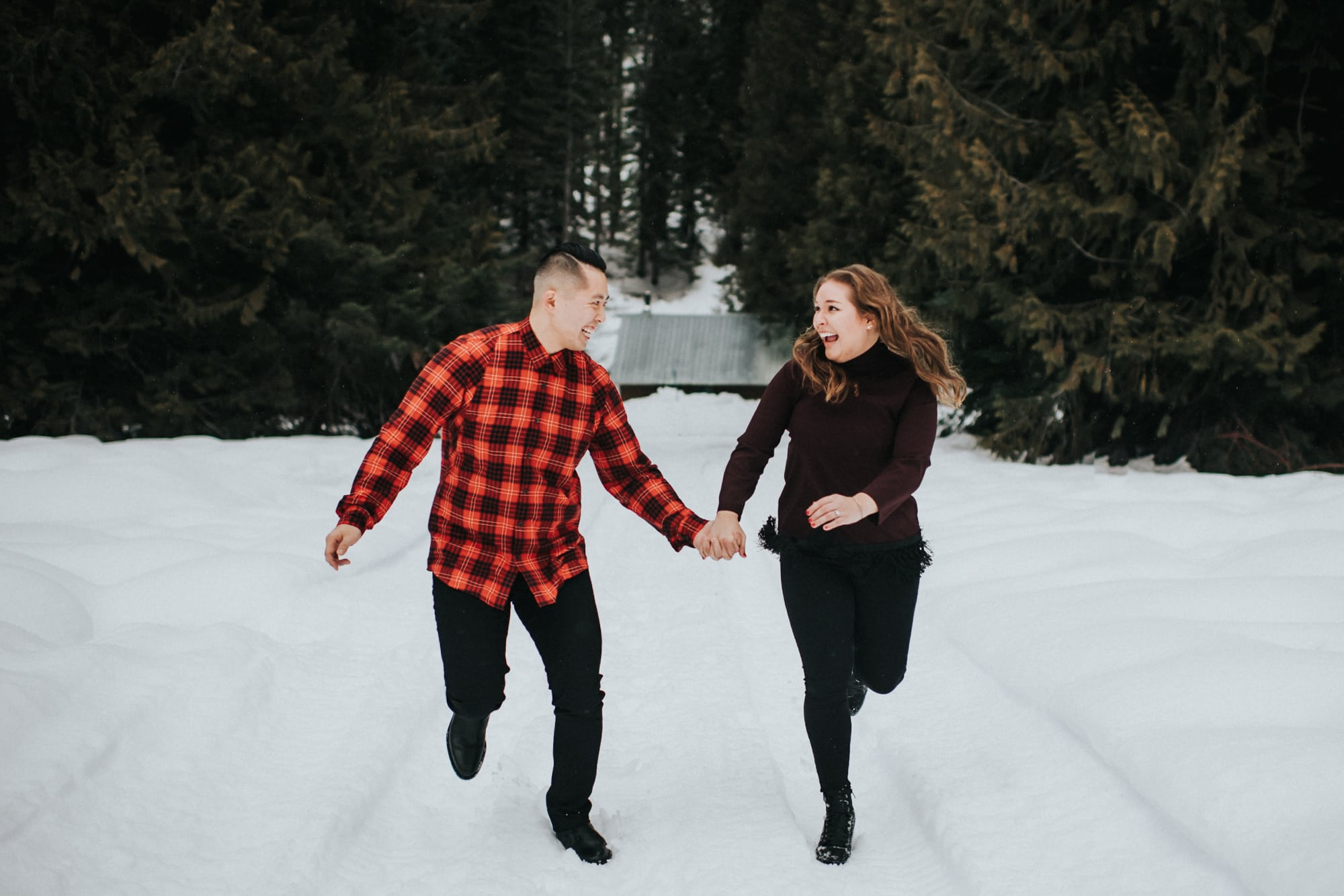 a couple running in the snow at tall timber ranch