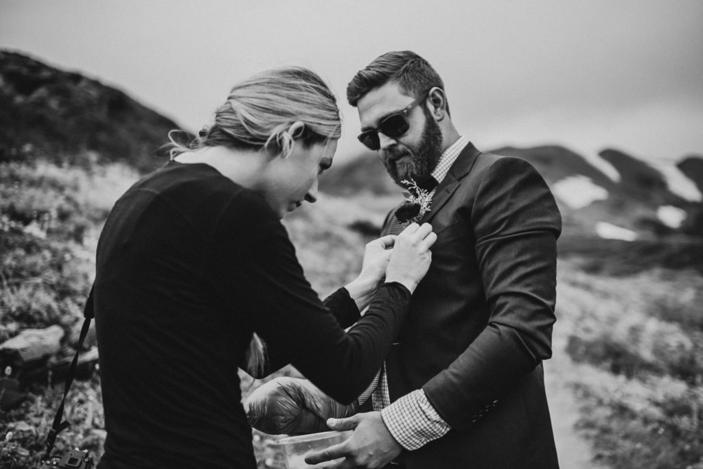 black and white of groom getting his boutonniere on