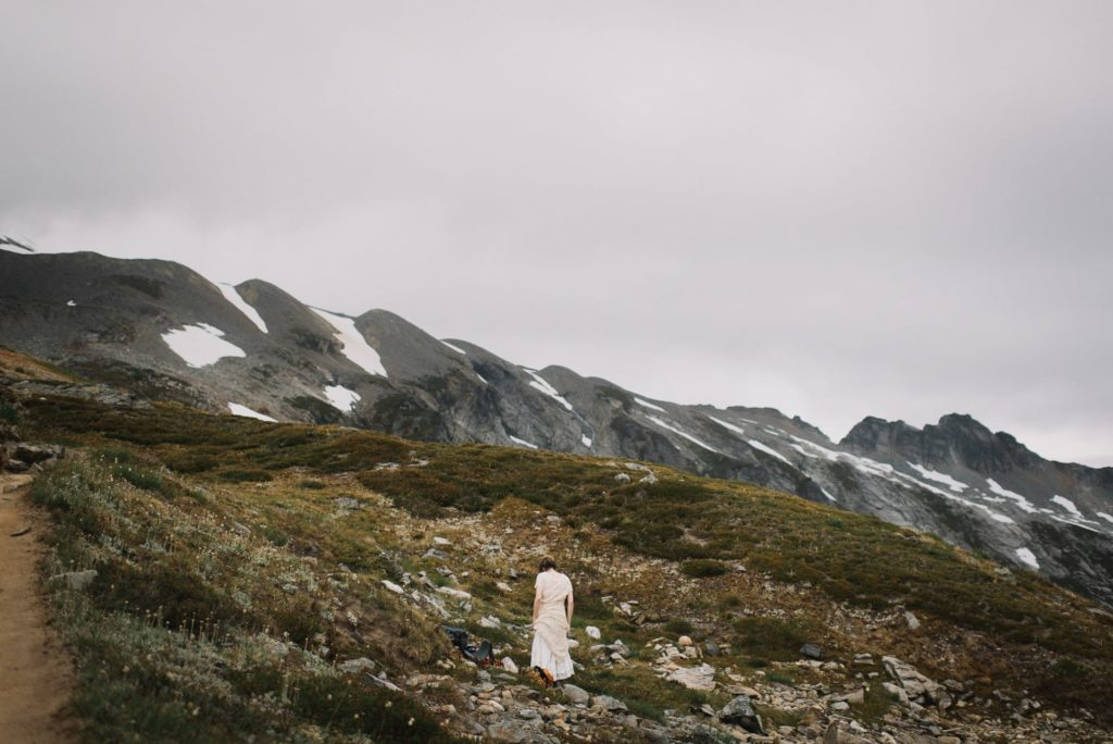 bride walking toward the mountains at her Sahale arm elopement
