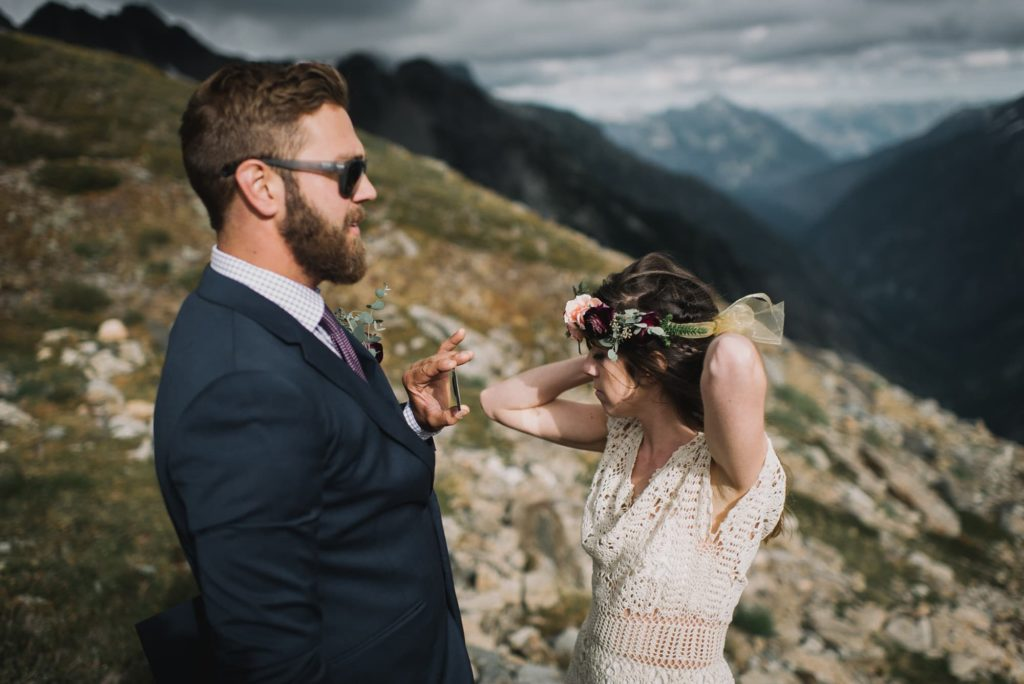 groom holding the mirror while bride puts on her flower crown