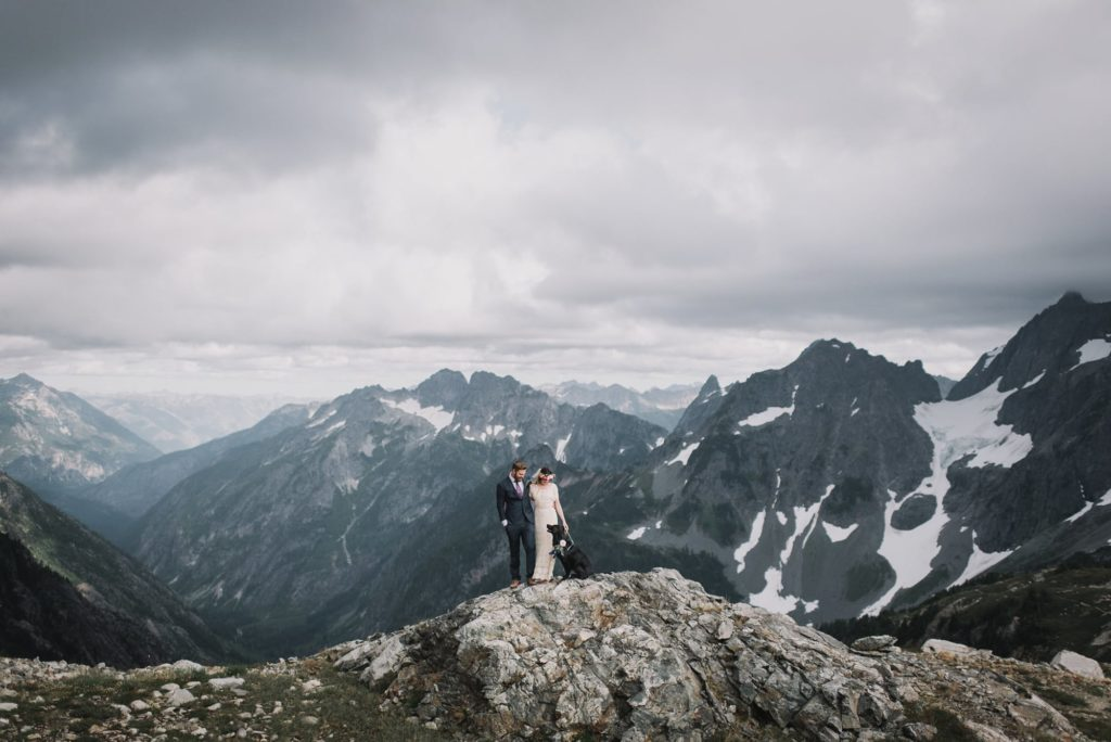 wide shot of the bride and groom looking down at the dog with mountains in the background
