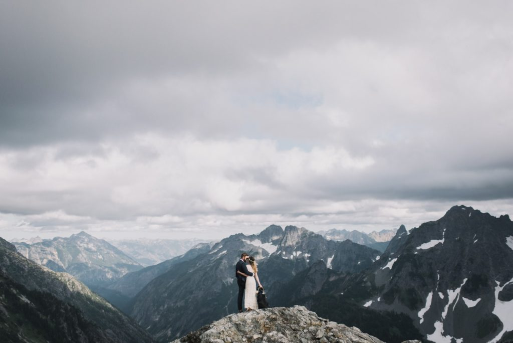 bride and groom facing the mountains with arms around eachother at sahale arm elopement