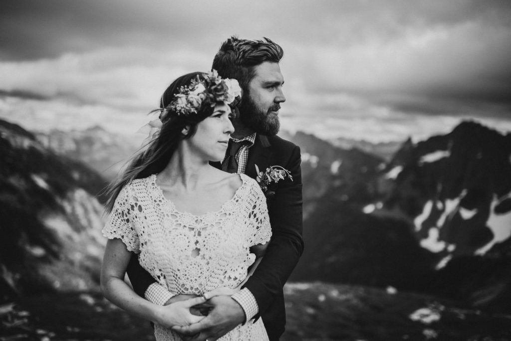 black and white of bride and groom looking at the mountains