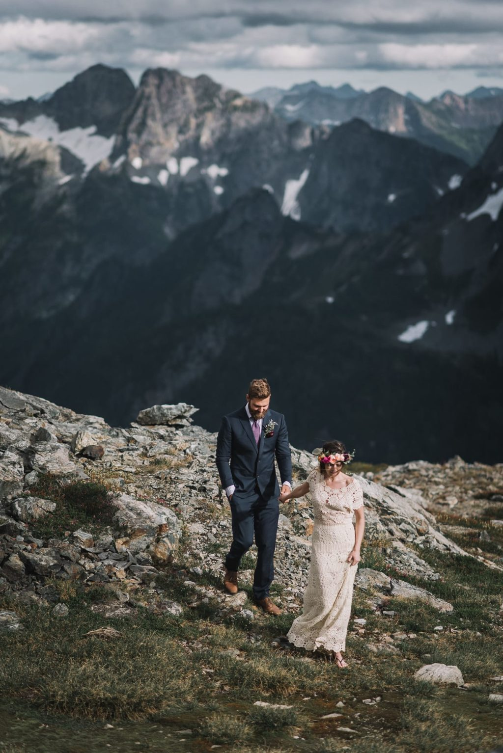 Bride and groom walking away from the mountains