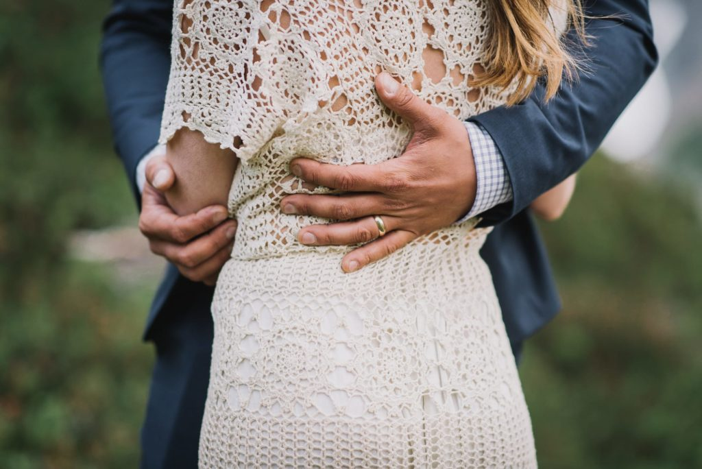 closeup of groom's hand around bride's waist