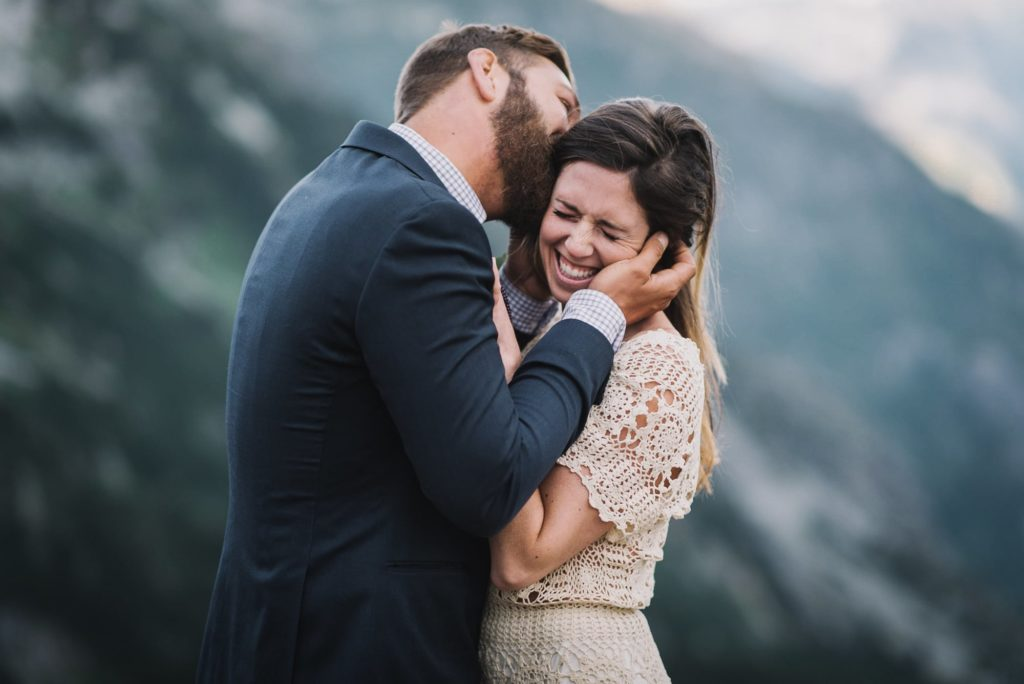 groom kissing bride's face while she laughs