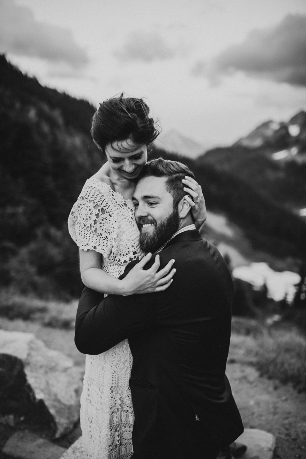 black and white of groom hugging bride and smiling
