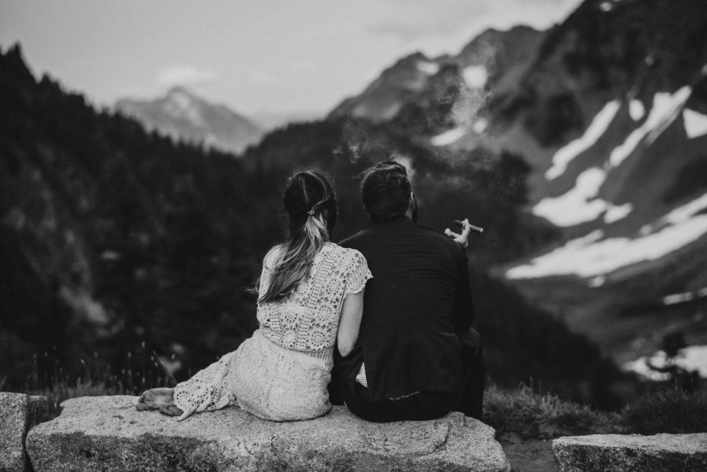 black and white of bride and groom looking out at the mountains