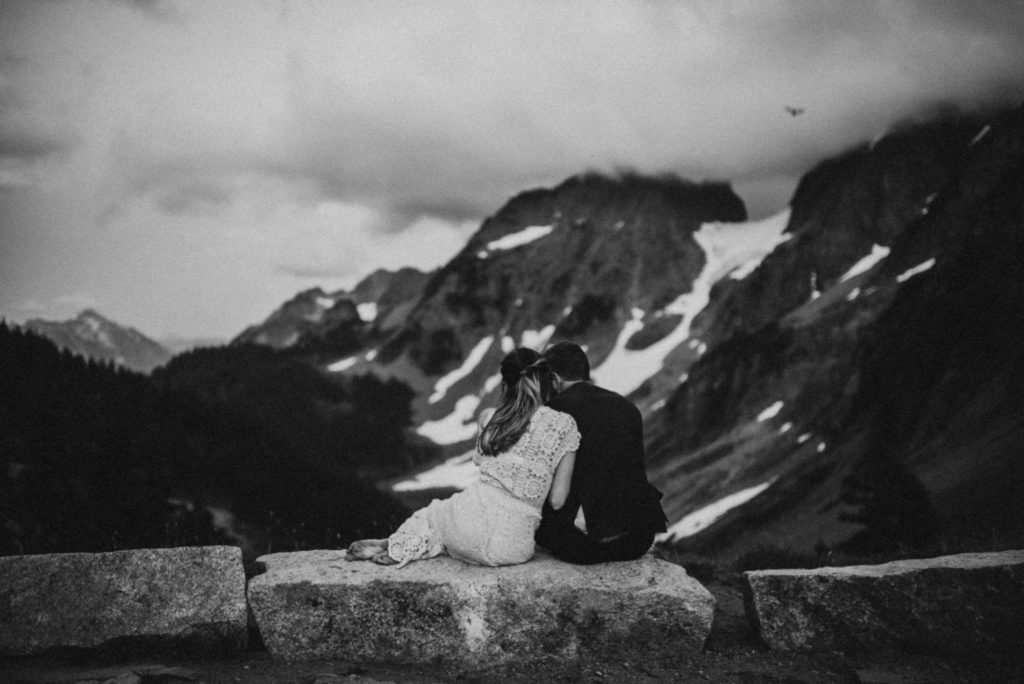 black and white of groom and bride looking out at the mountains
