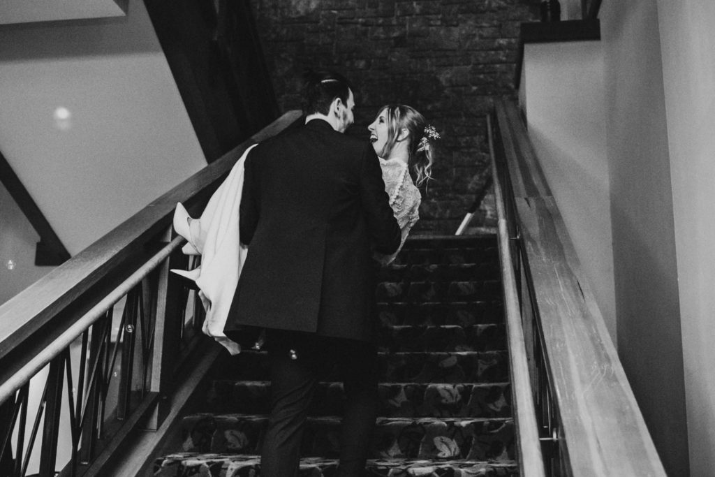 Groom carrying bride up the stairs