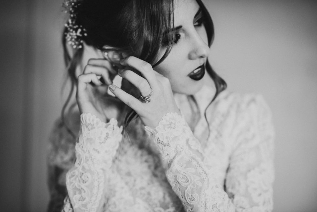 Black and white of bride putting on earrings