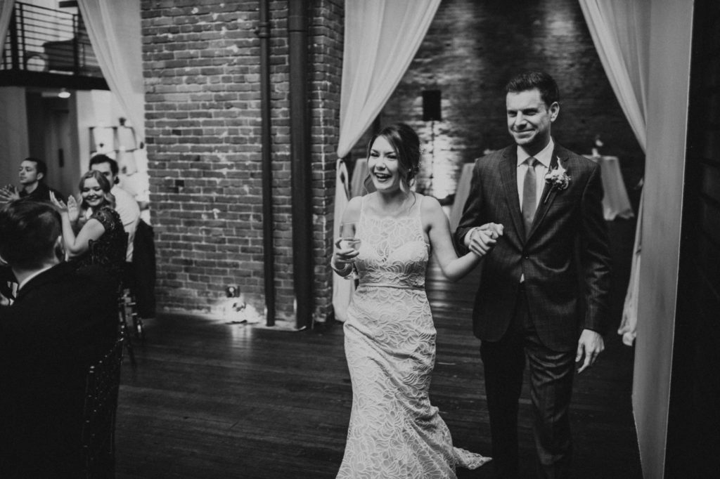 black and white of groom and bride walking into their reception