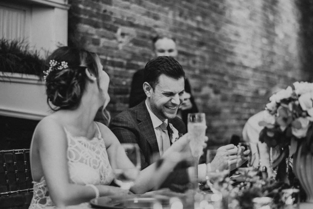 Black and white of groom laughing during speeches at Axis Pioneer square wedding