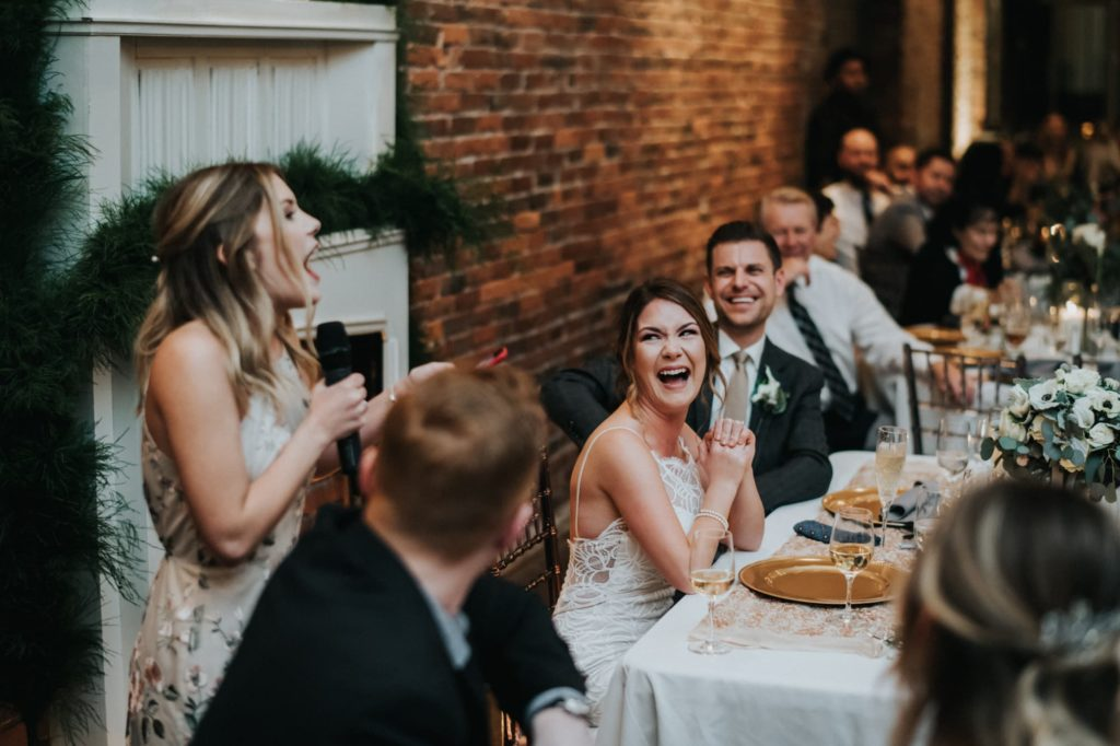 bride and groom laughing while maid of honor gives speech