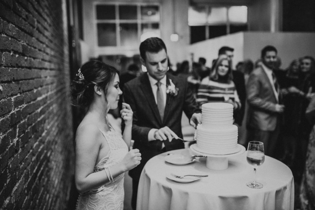 black and white of bride and groom getting ready to cut their cake