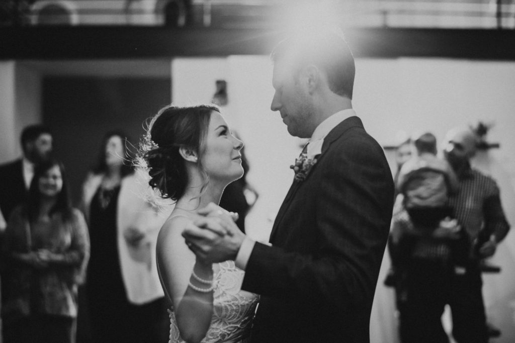 black and white of bride and groom dancing