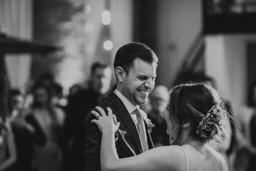 black and white of groom laughing while bride and groom dance