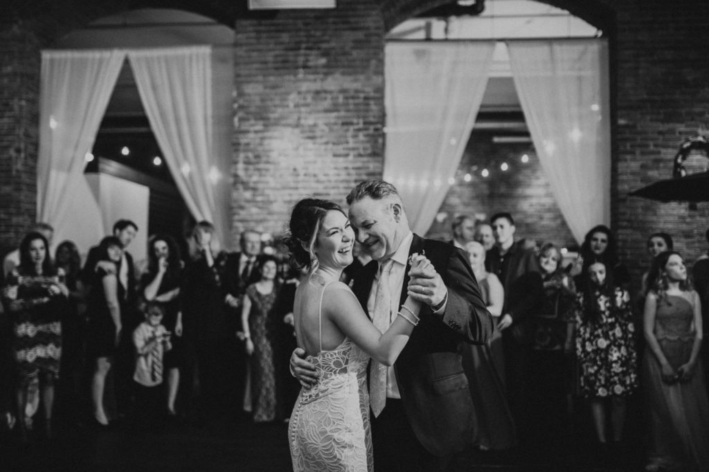 black and white of bride laughing while she dances with her father