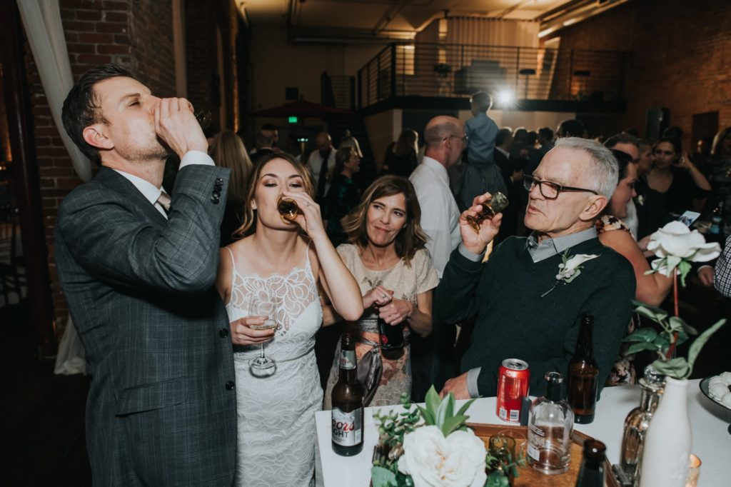 bride and groom taking shots with guests at the reception