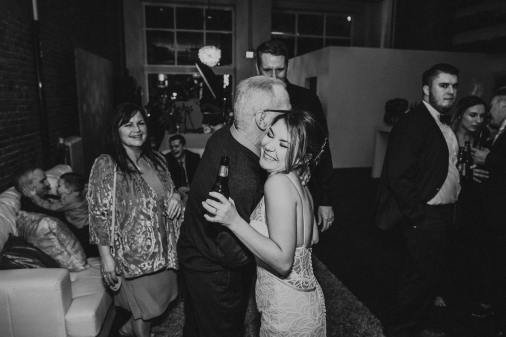 black and white of bride hugging a guest at the reception