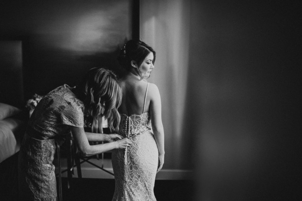 black and white of bride getting dress zipped up at Axis Pioneer Square wedding