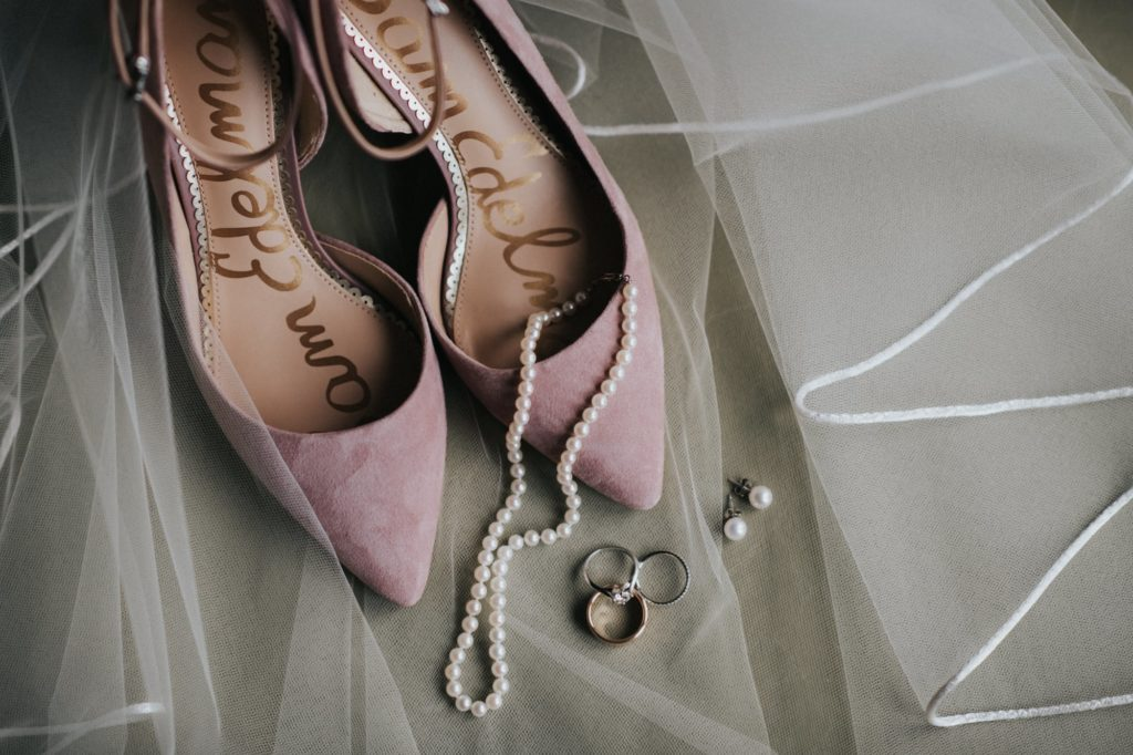 Closeup shot of shoes, rings, earrings and pearl necklace