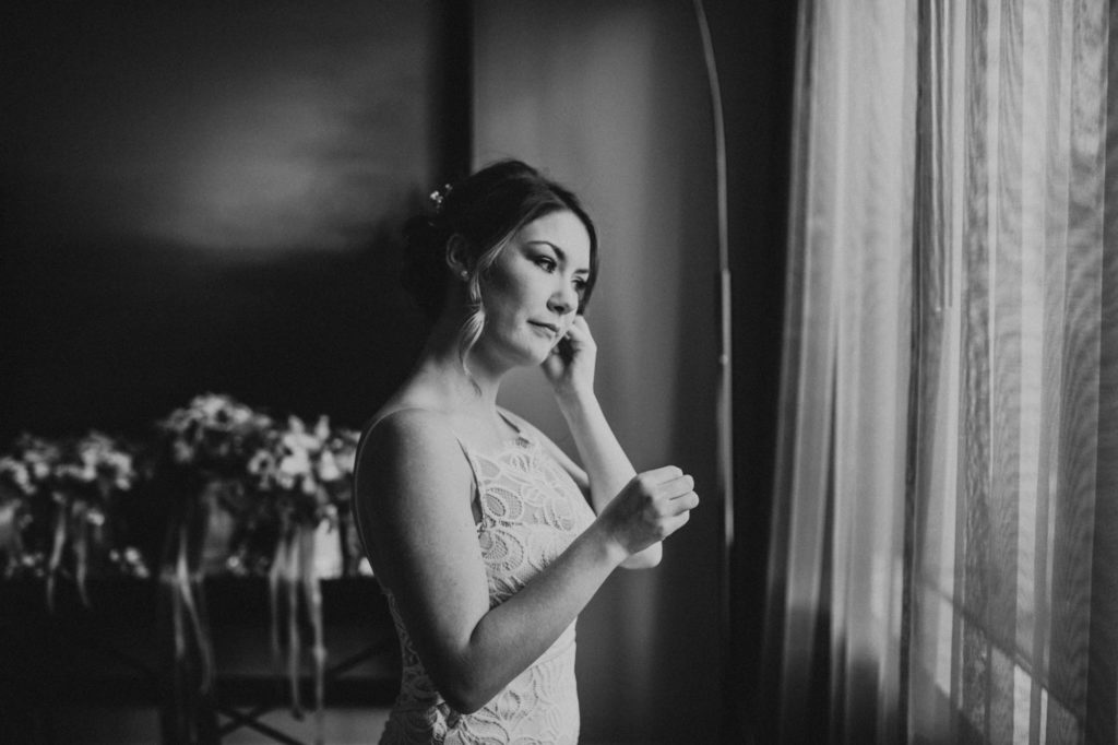 Black and white of bride putting earrings on