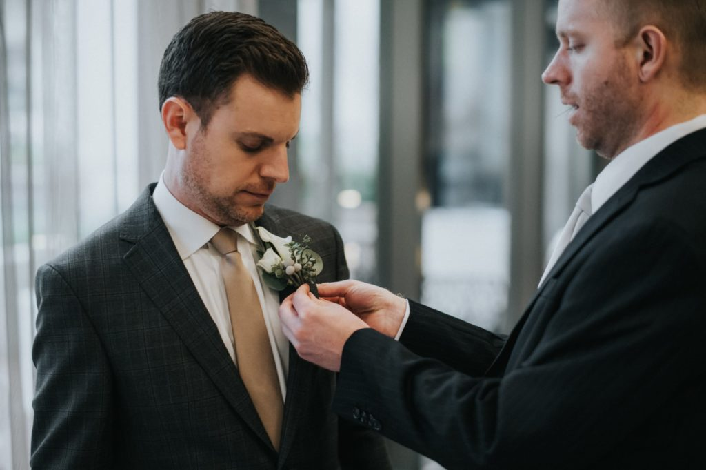 Groom getting boutonniere on