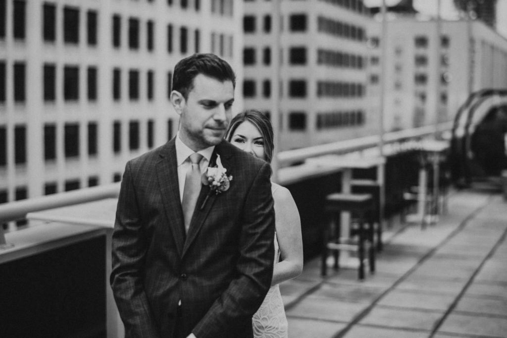 Black and white of bride behind groom