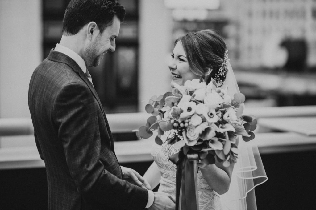 black and white of bride and groom laughing