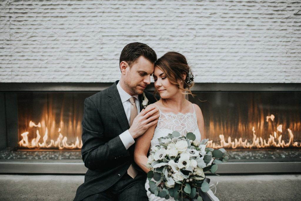 bride and groom sitting in front of fireplace