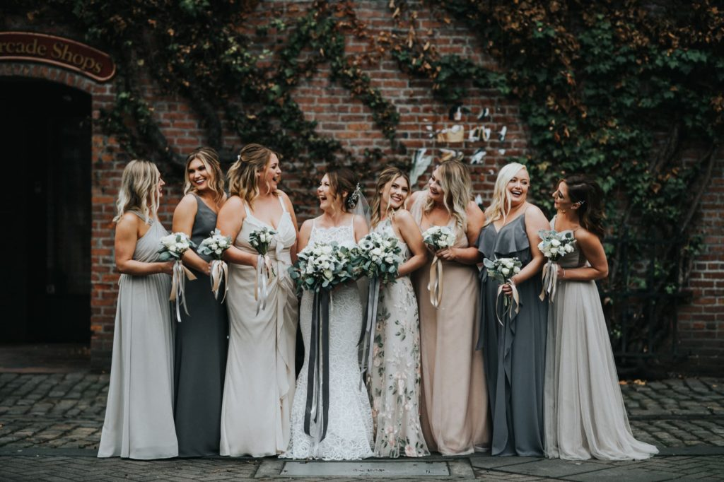 bride and bridesmaids laughing and looking at each other