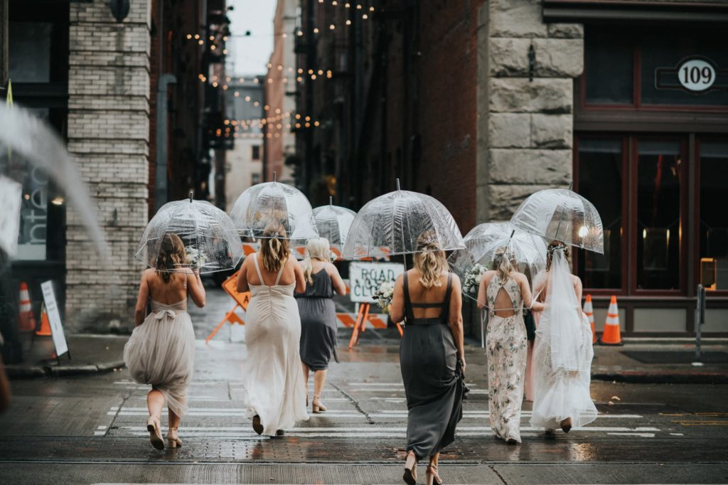 bridesmaids crossing the street in the rain