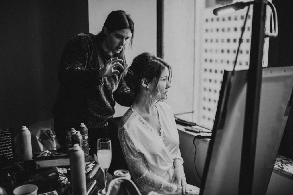 Black and white of bride getting hair done