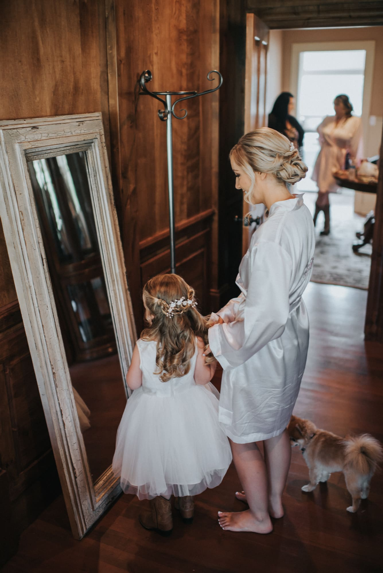 bride and flower girl getting ready together for wedding