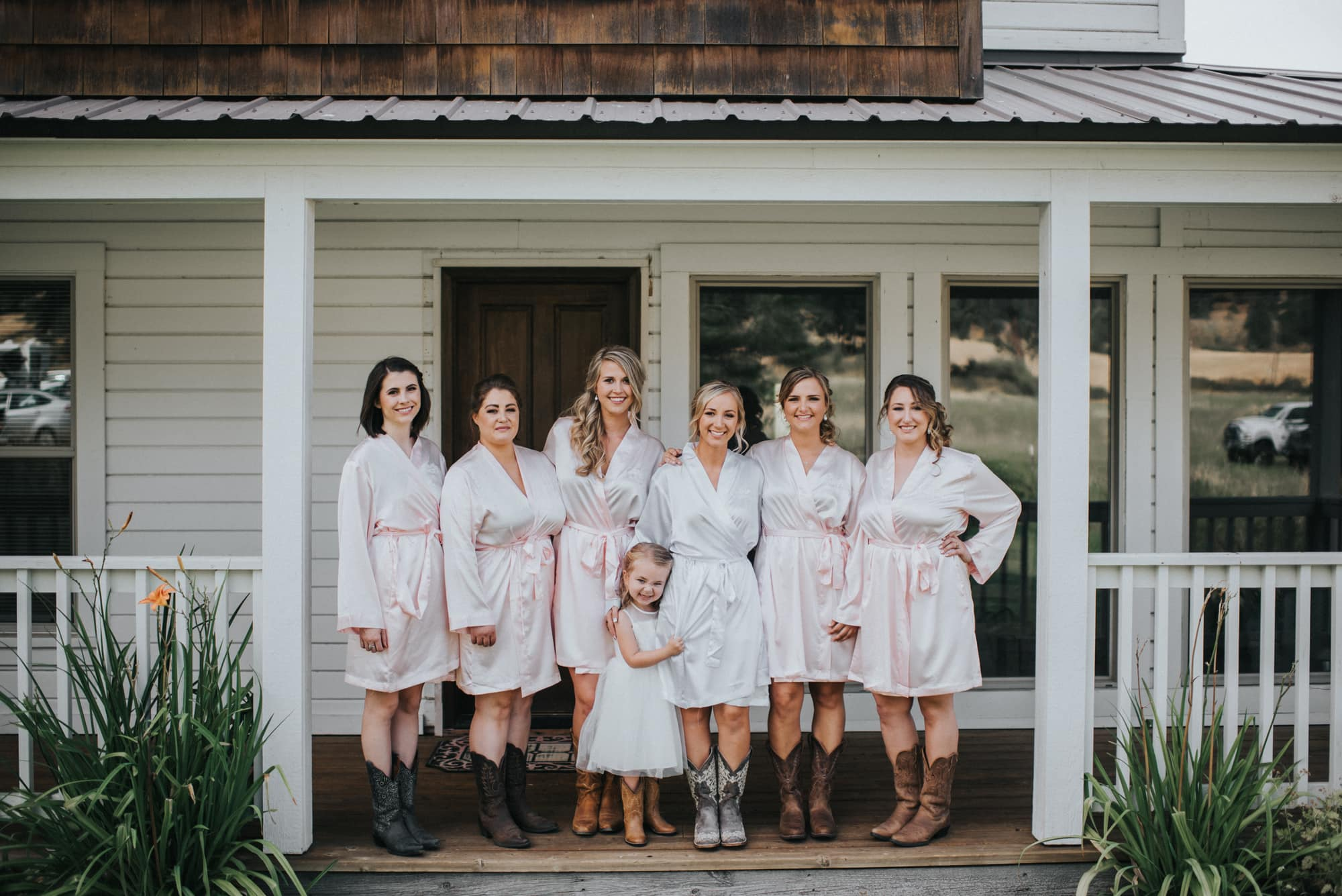 bride with bridesmaids on front porch at the cattle barn