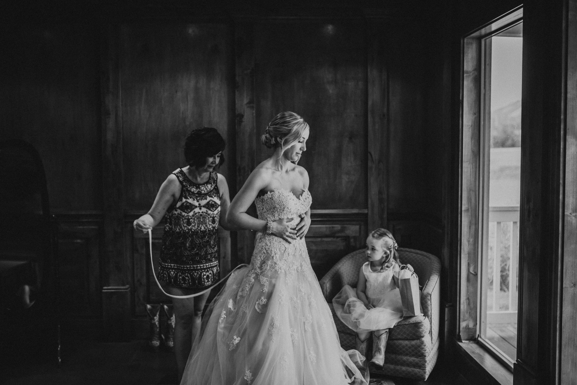 bride getting into dress in the farmhouse at the cattle barn
