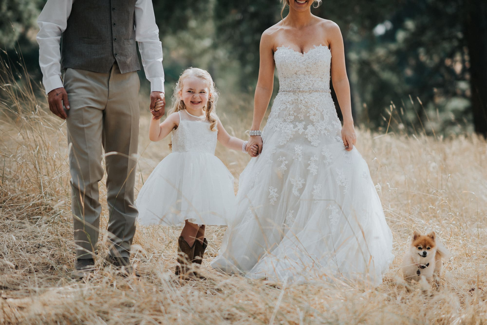 bride and groom taking photos with their daughter and their dog