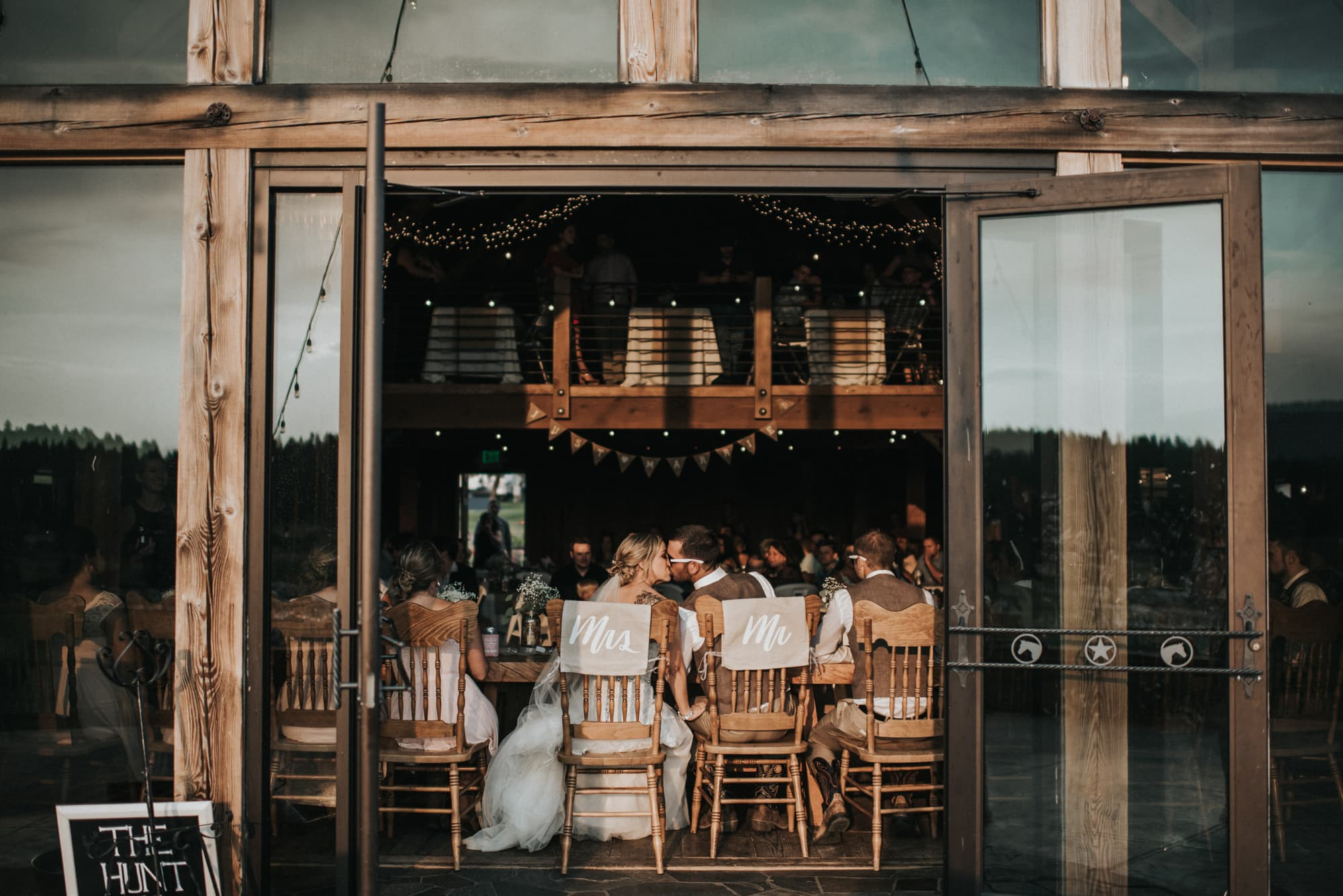 bride and groom kissing at head table at the cattle barn