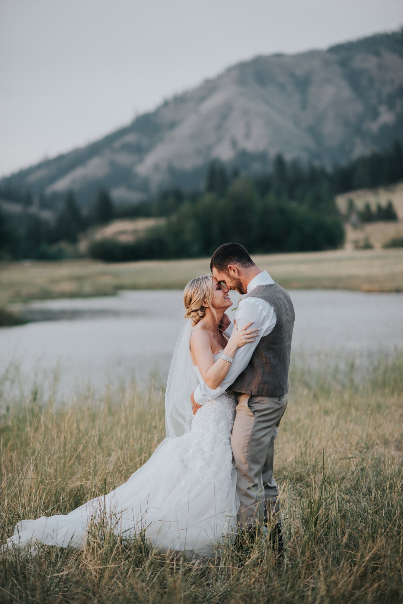 bride and groom portraits at the cattle barn with mountains in the background