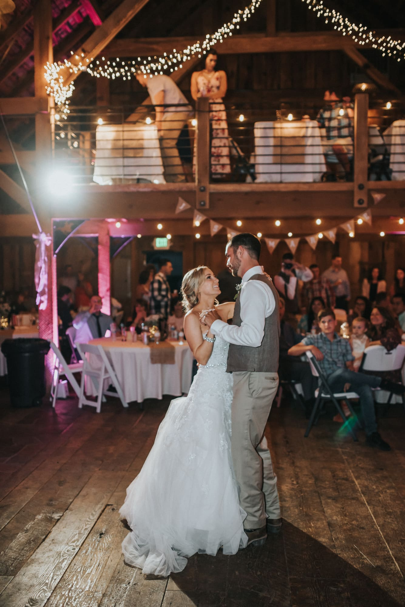 bride and groom have first dance inside barn