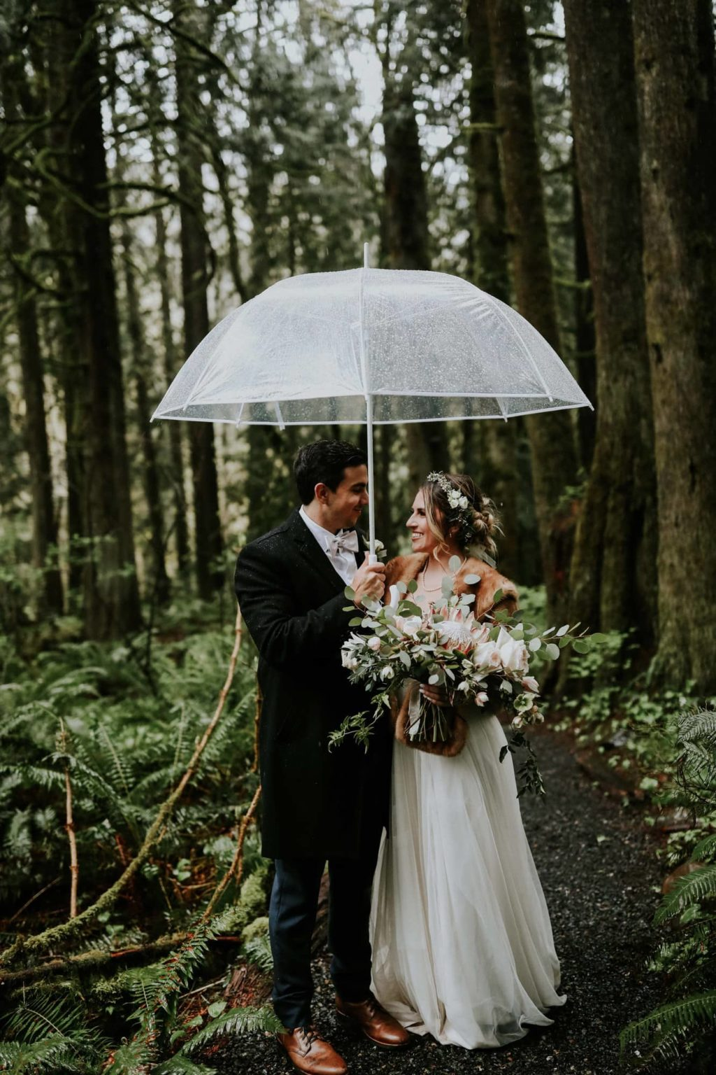 bride and groom looking at each other under an umbrella
