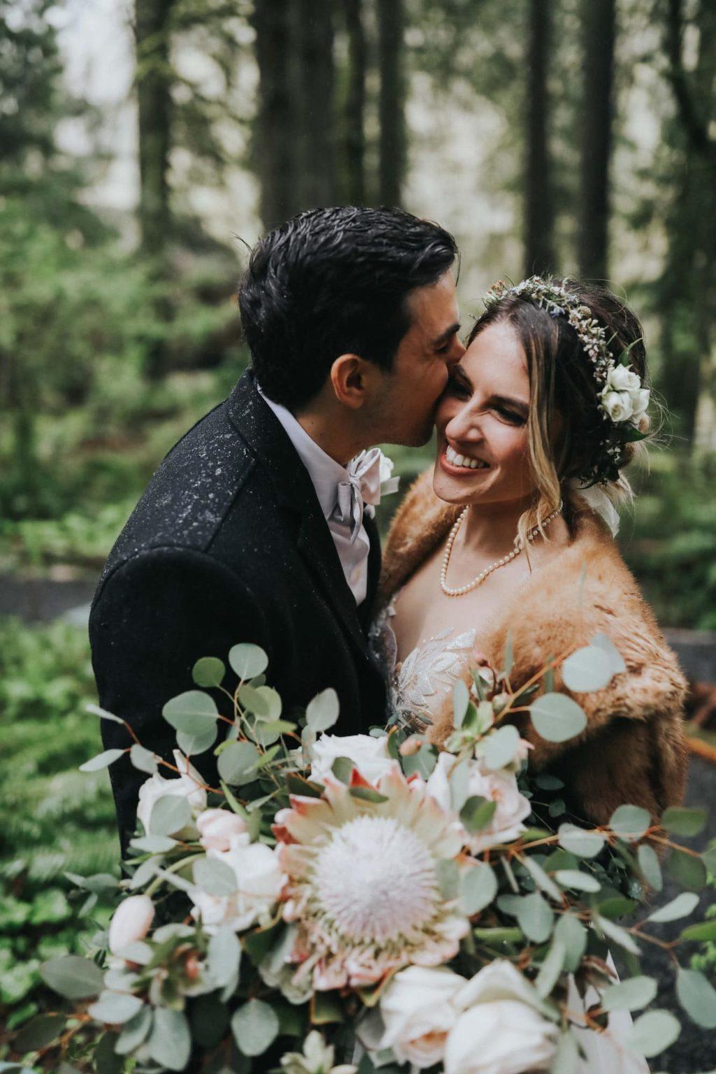 groom kissing bride's cheek while bride laughs