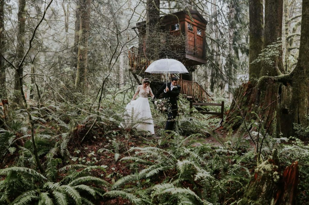 Bride and groom walking past treehouse