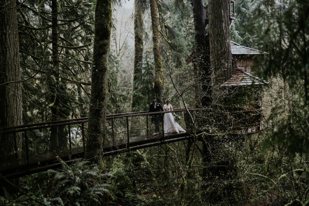 bride and groom walking down a suspension bridge at their treehouse point wedding