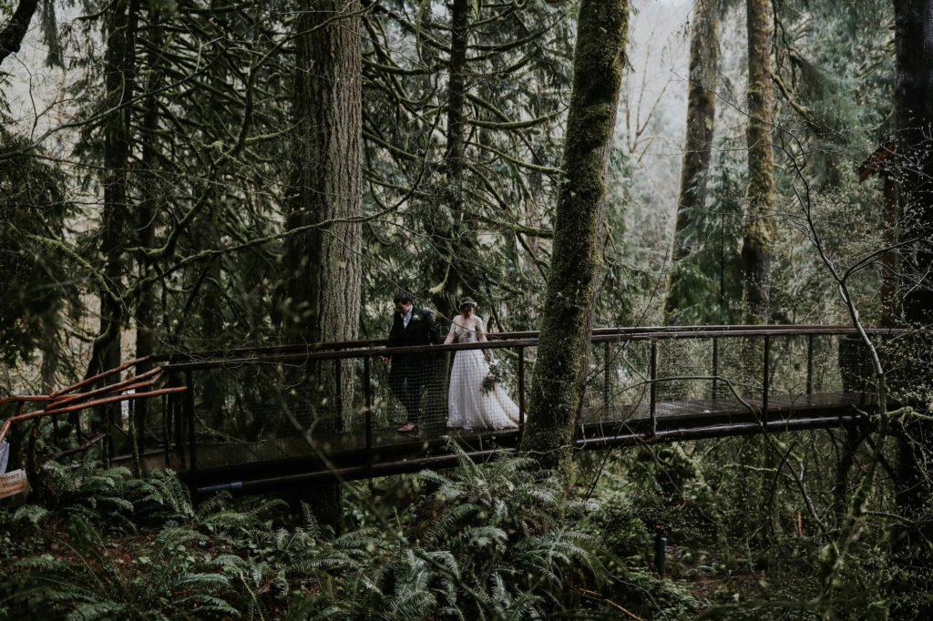 Bride and Groom walking across a bridge on their rainy wedding day